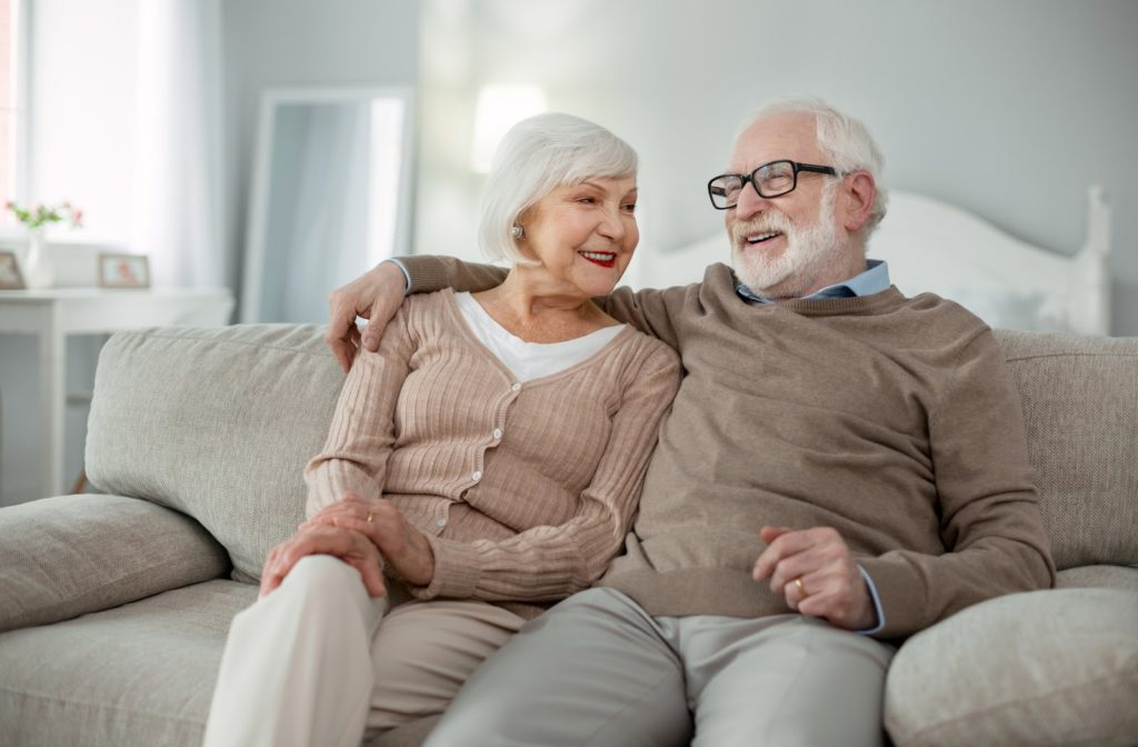 Happy senior couple sitting beside one another on couch at senior community.