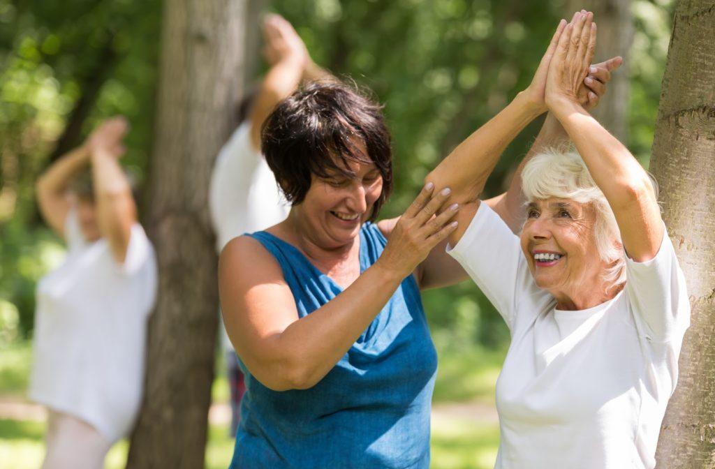 Instructor helping happy senior with yoga pose outside at senior community.